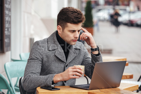 Portrait of working man sitting with silver laptop in cafe outsi Stock photo © deandrobot