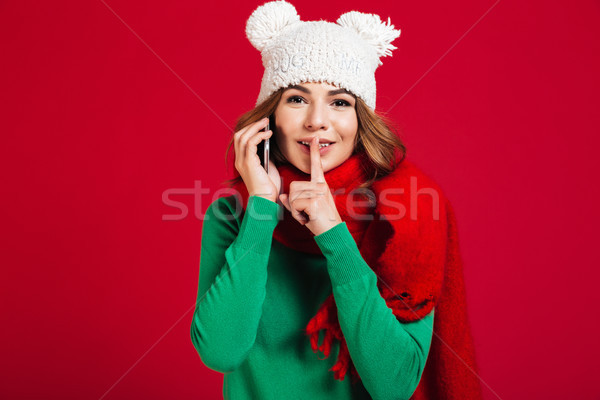 Woman showing silence gesture talking by phone. Stock photo © deandrobot