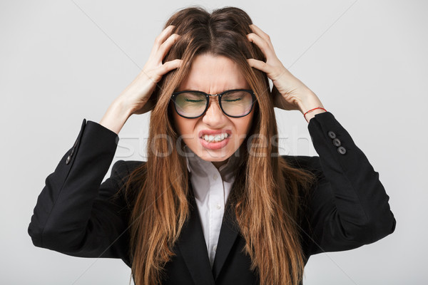 Young lady with closed eyes holding her head with hands isolated Stock photo © deandrobot