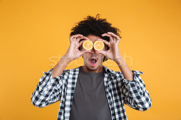 Portrait of a funny young african man holding sliced orange Stock photo © deandrobot