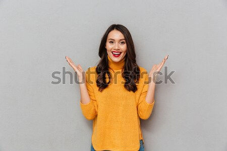 Pleased brunette woman in sweater with arm on hip Stock photo © deandrobot