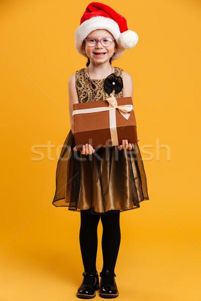 Cheerful girl child wearing christmas santa hat holding surprise Stock photo © deandrobot