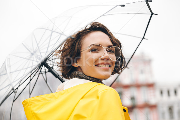 Smiling woman in yellow raincoat and glasses taking pleasure in  Stock photo © deandrobot