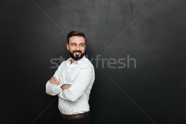 Portrait of cheerful good-looking man standing with arms folded, Stock photo © deandrobot