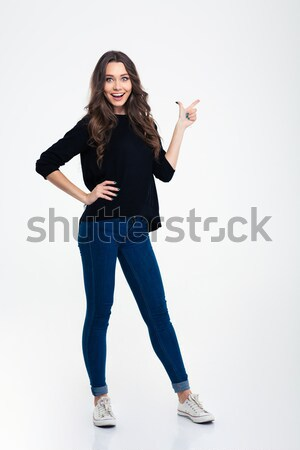 Photo of pleased woman with long brown hair sitting with legs cr Stock photo © deandrobot