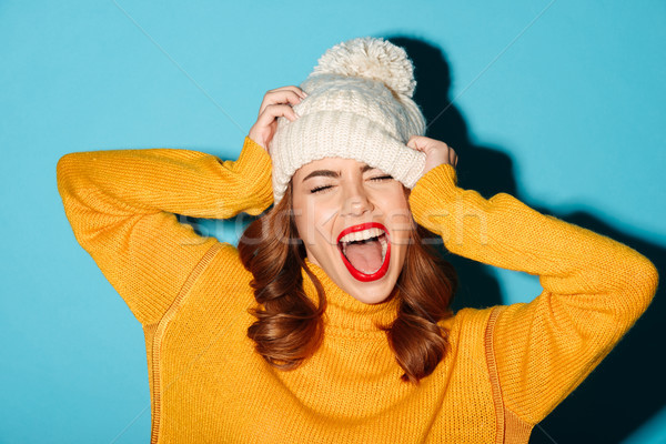 Portrait of a happy young girl dressed in winter hat Stock photo © deandrobot
