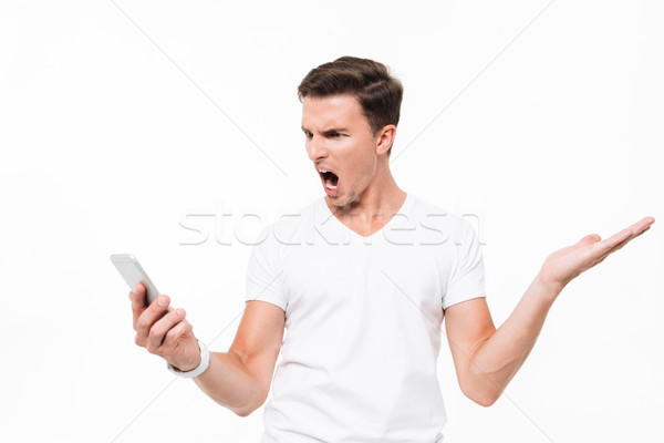 Portrait of an angry furious man in white t-shirt Stock photo © deandrobot