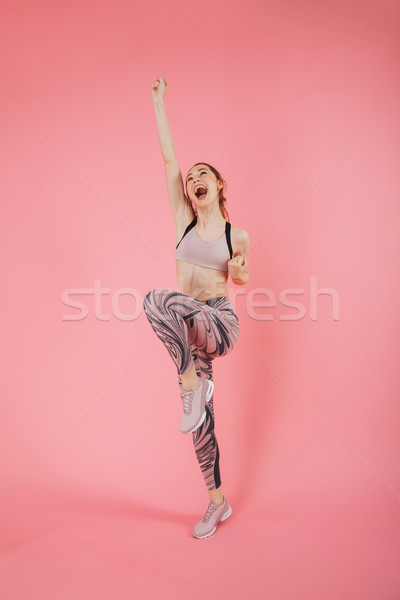 Full length image of screaming sportswoman rejoices and looking up Stock photo © deandrobot