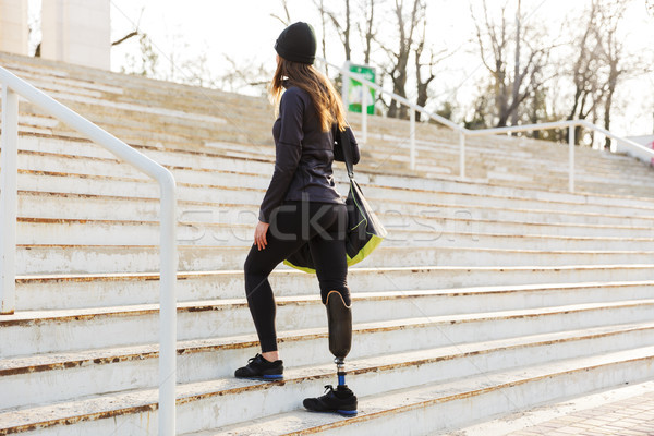 Photo from back of young athletic disabled girl with prosthetic  Stock photo © deandrobot