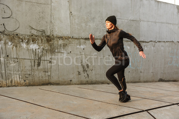 Photo of disabled sportswoman with prosthetic leg in tracksuit,  Stock photo © deandrobot