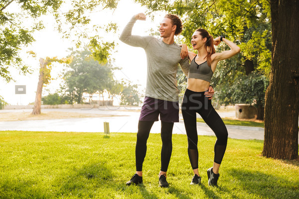 Photo of joyful sportive people man and woman 20s in sportswear, Stock photo © deandrobot