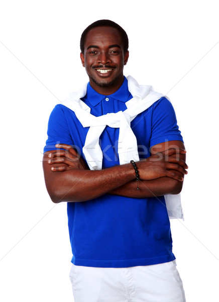 Smiling african man standing with arms folded over white background Stock photo © deandrobot