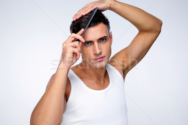 Serious man combing his hair over gray background Stock photo © deandrobot