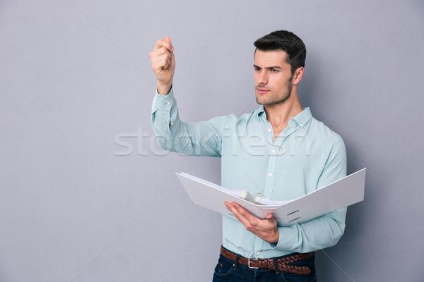 Pensive young man holding folder Stock photo © deandrobot