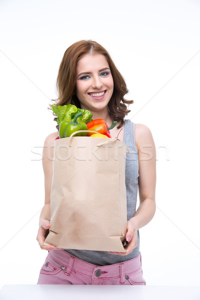 Happy woman holding a shopping bag full of groceries and looking on at camera Stock photo © deandrobot