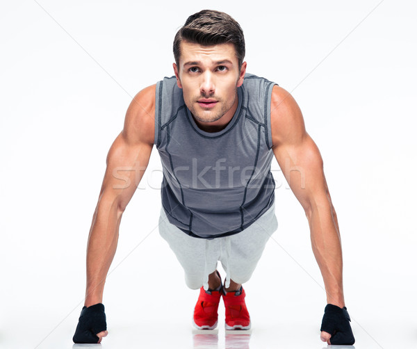 Fitness young man doing push ups Stock photo © deandrobot