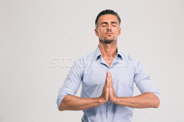 Businessman praying with closed eyes  Stock photo © deandrobot