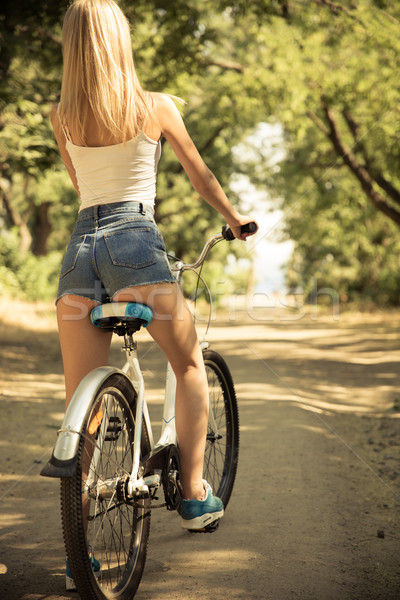 Woman riding on bicycle outdoors Stock photo © deandrobot