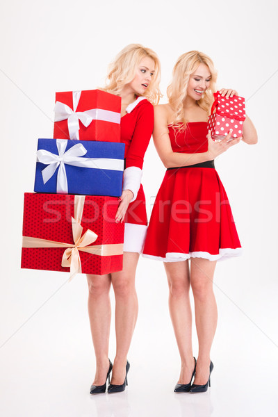 Two sisters twins in santa costumes holding and opening presents  Stock photo © deandrobot