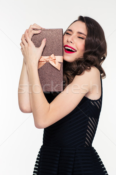 Excited elated pretty woman with retro hairstyle hugging gift box Stock photo © deandrobot