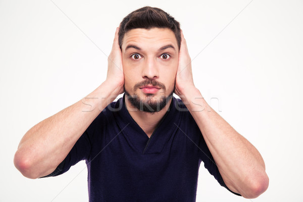 Portrait of dazed bearded young man closed ears by hands Stock photo © deandrobot