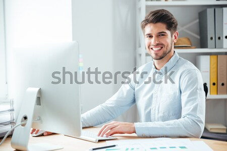 Happy male designer sitting and drawing on graphic tablet  Stock photo © deandrobot
