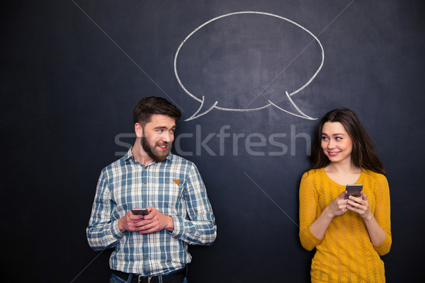 Couple using smartphones over blackboard with speech dialogue Stock photo © deandrobot