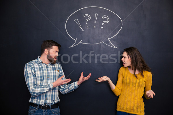 Unhappy couple quarreling over blackboard background Stock photo © deandrobot