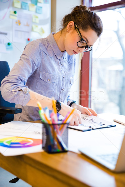 Focused woman fashion designer drawing sketches on workplace Stock photo © deandrobot