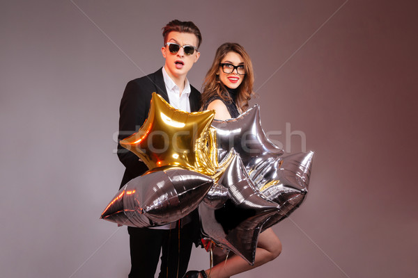 Beautiful young couple standing and holding star shaped balloons Stock photo © deandrobot