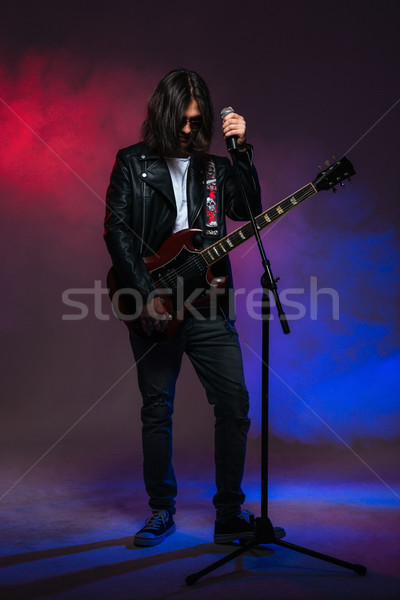 Singer with long hair singing in microphone and playing guitar  Stock photo © deandrobot