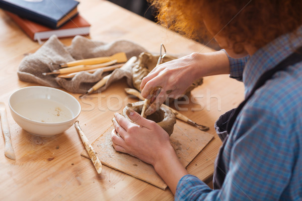Concentrated curly young woman working on clay pot Stock photo © deandrobot