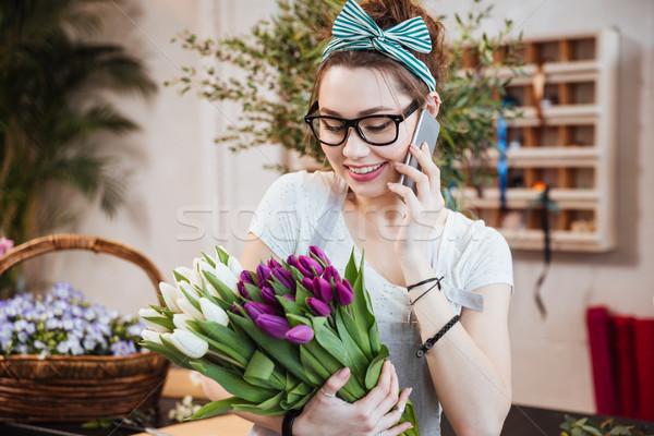 Donna fiorista bouquet tulipani parlando cellulare Foto d'archivio © deandrobot