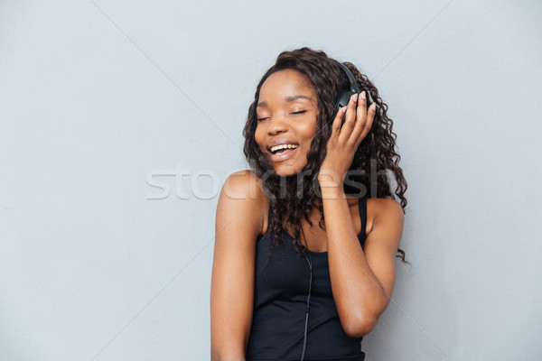 Woman with closed eyes listening music in headphones Stock photo © deandrobot