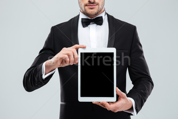 Man in tuxedo with bowtie holding blank screen tablet Stock photo © deandrobot