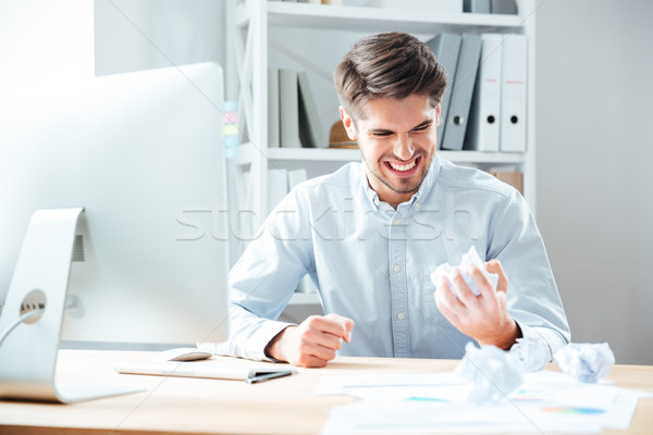 Mad annoyed businessman working and crumpling paper in office Stock photo © deandrobot