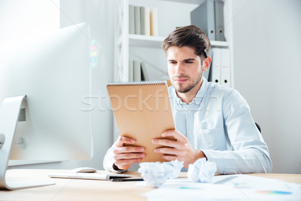 Handsome young businessman man sitting and reading notes in notebook Stock photo © deandrobot