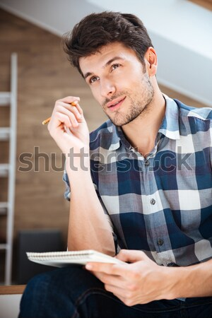 Close up portrait of a young handsome man sitting Stock photo © deandrobot