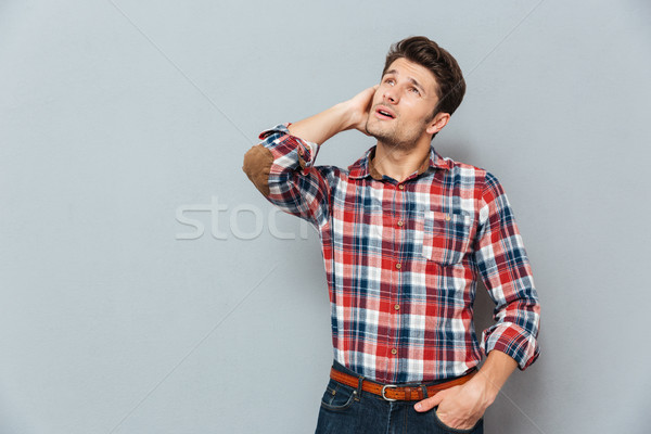 Wondered happy young man with mouth opened looking up Stock photo © deandrobot