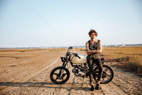 Young brutal man leaning on a motorcycle Stock photo © deandrobot