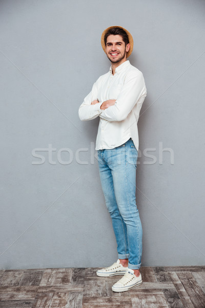 Smiling confident young man in hat standing with hands folded Stock photo © deandrobot