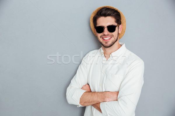 Alegre hombre sombrero gafas de sol pie manos Foto stock © deandrobot