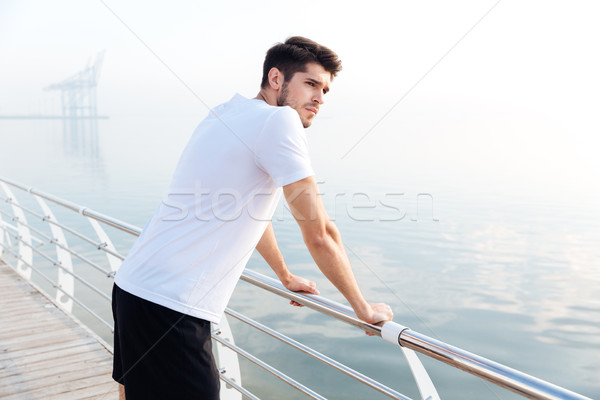 Sportsman standing on pier and looking at the sea Stock photo © deandrobot