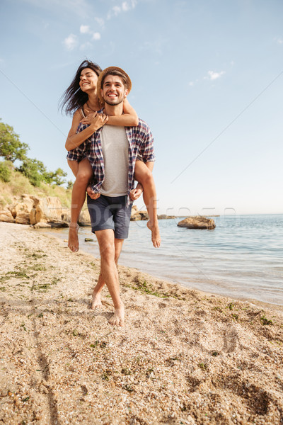 Man giving piggy back ride to his girlfriend at beach Stock photo © deandrobot