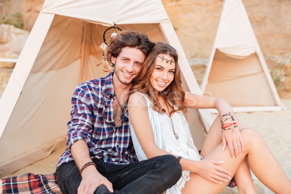 Beautiful young couple sitting in teepee on the beach Stock photo © deandrobot