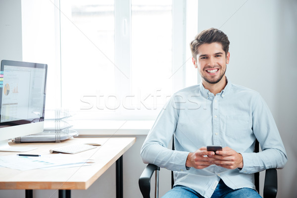 Businessman sitting at the table and using smartphone in office Stock photo © deandrobot