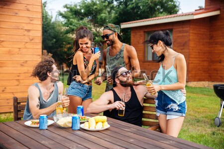 улыбаясь люди говорили питьевой пива таблице улице Сток-фото © deandrobot