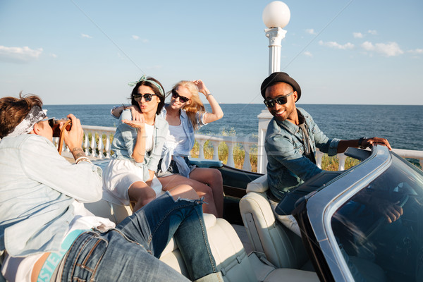 Multiethnic group of happy young people taking photos in cabriolet Stock photo © deandrobot