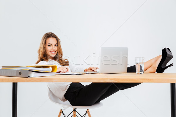 Cheerful businesswoman sitting and using laptop with legs on table Stock photo © deandrobot
