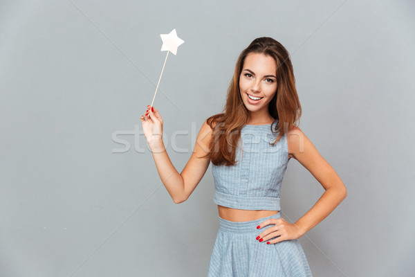 Cheerful beautiful young woman holding magic wand Stock photo © deandrobot